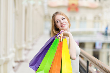 A happy smiling young lady with a lot of colourful shopping bags from the fancy shops.