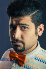Portrait of hispanic / middle eastern serious man with orange bow tie and fashion haircut and beard looking at camera with frown face on studio.