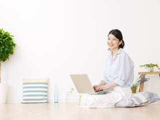部屋でノートパソコンを使う女性