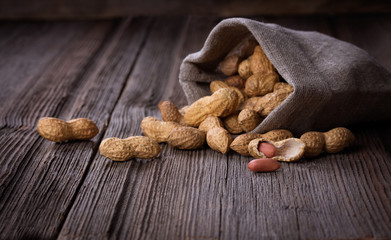peanuts in a miniature burlap bag on wooden surface