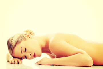 Side view of a nude woman lying on the floor with closed eyes