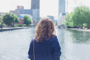 Woman looking at water in city