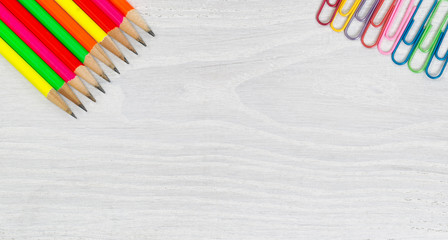 Bright colorful pencils and paper clips on white wooden desktop