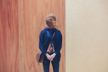 Young woman standing by two colored wooden wall