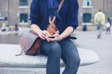 Woman sitting on granite bench using smart phone