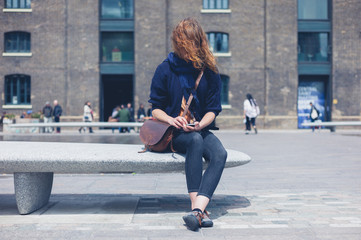 Woman sitting on granite bench using smart phone