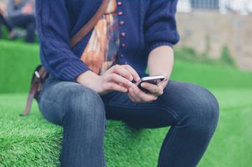 Woman sitting on astro turf using smart phone