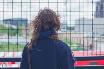 Young woman by wire fence