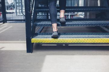 Woman walking up metal stairs