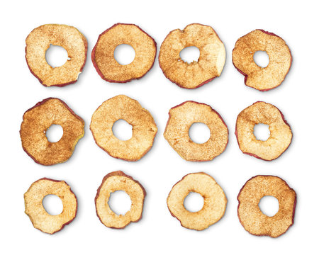 Dried apple rings sprinkled with cinnamon on white background.