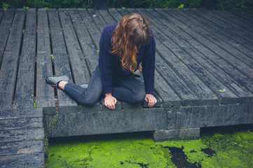 Woman sitting on wooden deck by pond