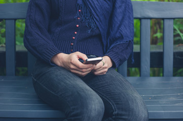 Woman sitting on bench using smart phone