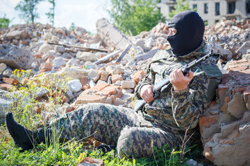 Military camouflage with a rifle on a background of bombed buildings.