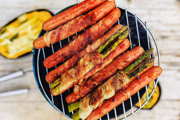 Grilled sausages and asparagus with bacon