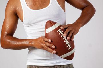 Man's arm holding an American football