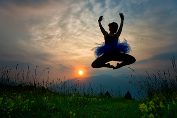 Girl dancer in nature at the sunset