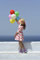 Young woman in dress holding colorful balloons at Santorini