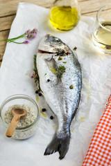 Fresh fish gilt-head bream dorade with salt and pepper