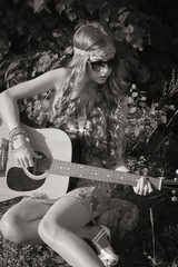 Young woman sitting on a field and playing guitar