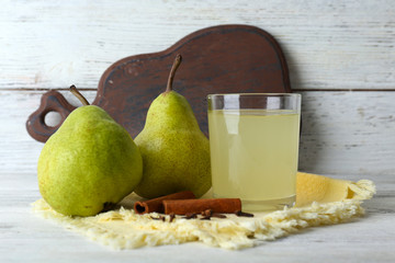 Pear juice with fresh fruits and cinnamon on wooden background