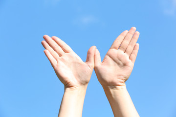 Female hands over blue sky background