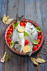 raw sea bream/dorado with tomato and lime, prepared for cooking