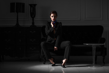 fashionable woman in black suit in dark minimalistic interior