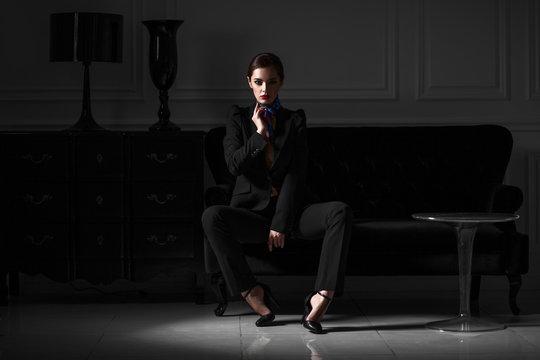 fashionable woman in black suit in dark minimalistic interior