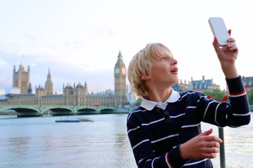 Boy making selfie photo in front of Houses of Parliament, Big Ben and River Thames on a summer evening at sunset, London, UK. Happy tourist kid enjoying view during family trip to England.