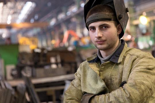 Portrait factory welder worker on manufacture workshop background