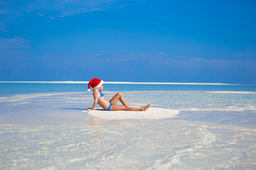 Little girl in Santa hat on the beach during vacation