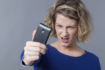 Unhappy frowning female teenager taking her selfie portrait on mobile phone
