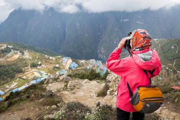 Wall Mural - Woman photographer  taking picture Namche Bazaar mountain village