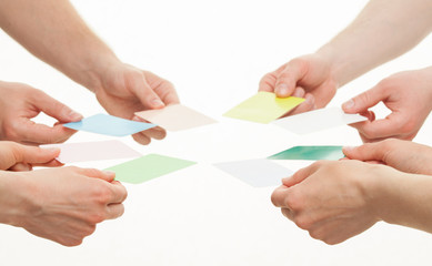 Human hands reaching out colorful paper cards
