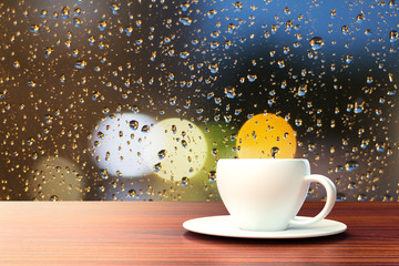 cup of coffee on the background of the window with raindrops