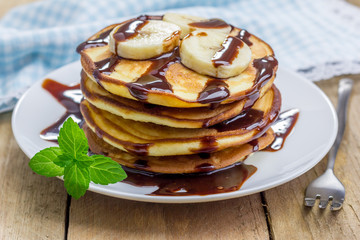 Stack of pancakes with banana and chocolate syrup