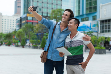 Two men tourists taking selfie photo smile, asian mix race