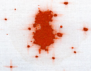 red stain on a white material with drops