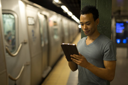 Young African Asian man in subway using tablet pc