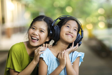 Two girls were sharing music on headphones.