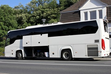 Reisebus mit geöffneten Gepäckfächern an Bushaltestelle
