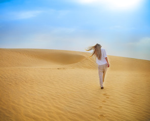 Beauty blond woman walking in Sahara desert. Tunisia.