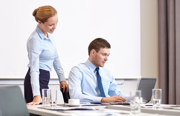 businessman and secretary with laptop in office