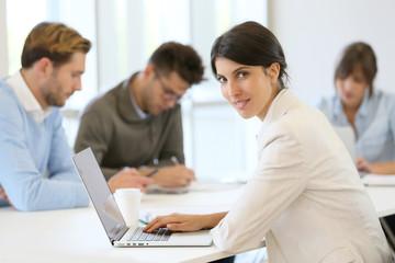 Businesswoman working on laptop, shared workspace