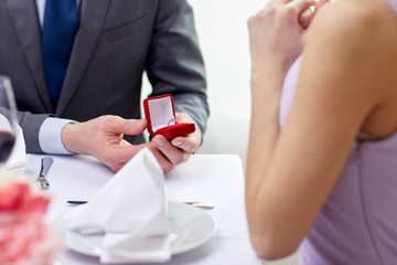 excited young woman and boyfriend giving her ring
