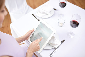 close up of woman with tablet pc at restaurant