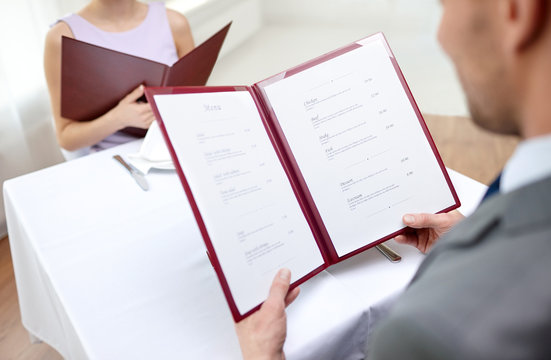 close up of couple with menu at restaurant