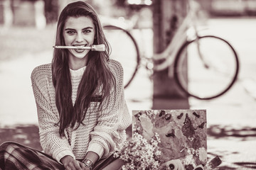 art stylish hipster woman keep brush in mouth outdoor portrait