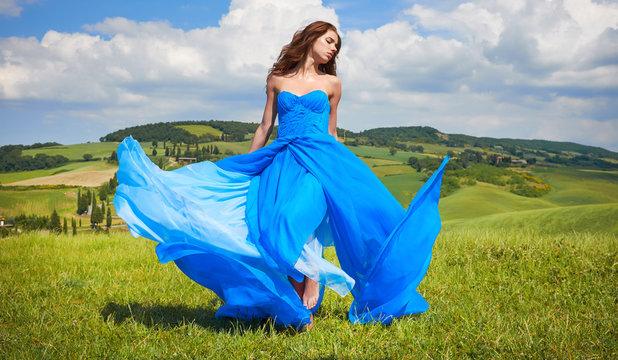 Portrait of a beauty woman in blue dress on Italy hills