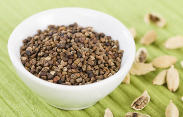 Cardamom Seeds - Bowl of cardamom seeds in a green background.